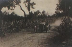 Un'auto, col n.6 di gara, che alza polvere su una strada affiancata da ricca vegetazione